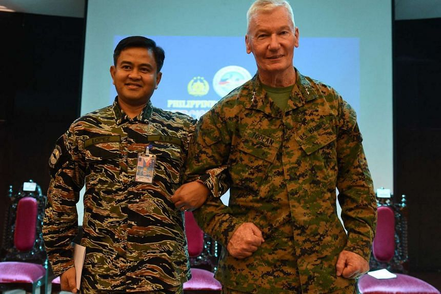 Philippine exercise director Vice-Admiral Alexander Lopez (left) and his US counterpart Lieutenant General John Toolan linking arms during the opening ceremony of the annual joint 11-day Balikatan (Shoulder-to-Shoulder) military exercise in Manila on