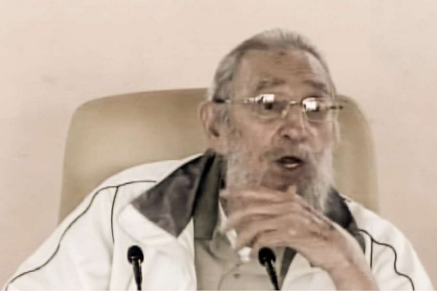 Former Cuban President Fidel Castro talks with students in a school of Havana, as seen in this TV screengrab.