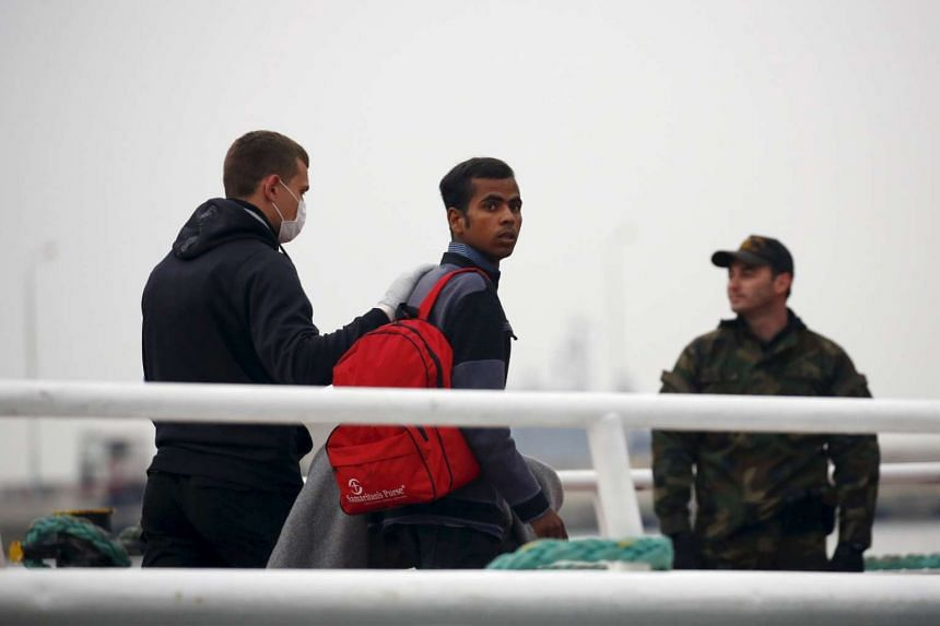 An officer (left) from the European Union border agency Frontex escorts a migrant boarding a Turkish-flagged passenger boat to be returned to Turkey on April 8, 2016.