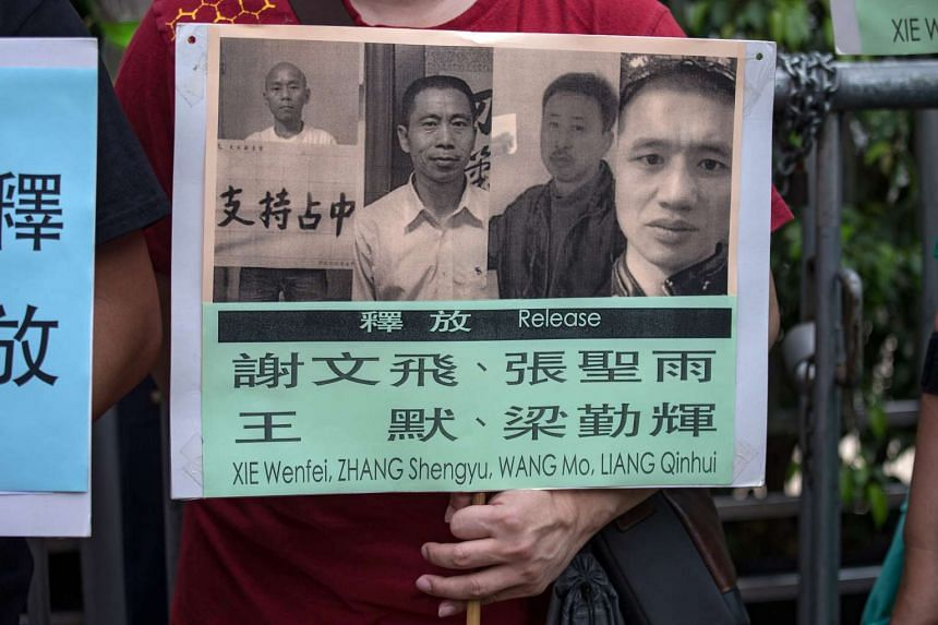 A protester holds a poster showing imprisoned mainland Chinese activists during a protest outside the China Liaison Office in Hong Kong, on April 8.