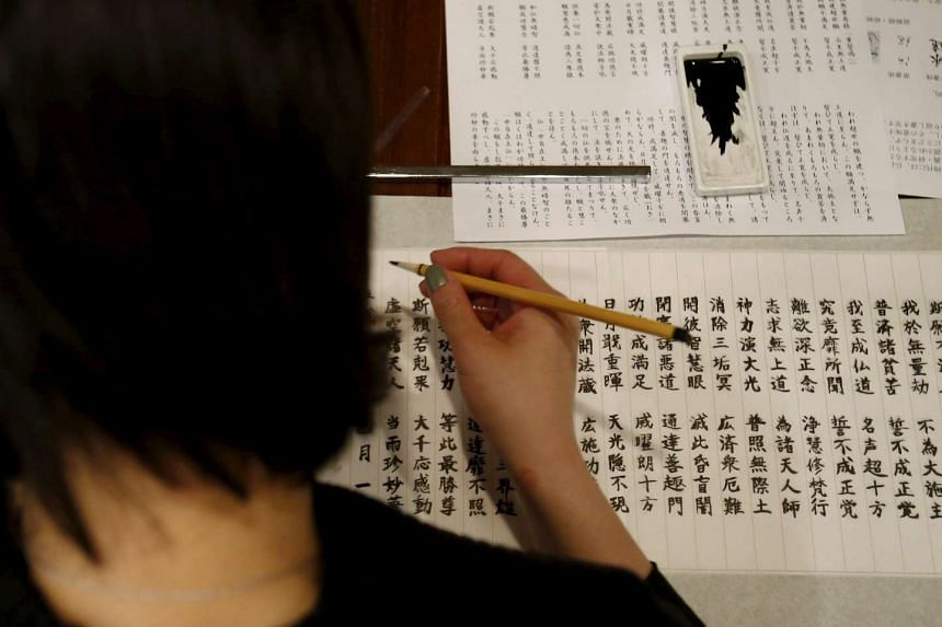 A visitor traces Buddhist sutras with a brush at Tera Cafe in Tokyo, Japan, on April 1, 2016.
