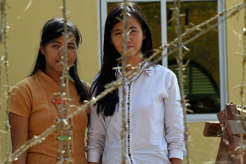 Detained Myanmar students (from left) Honey Oo, 28, and Phyo Phyo Aung, 27, outside the Tharrawady court house before their trial. They are among some 40 students facing charges including unlawful assembly.