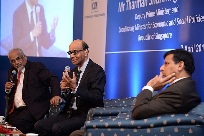 DPM Shanmugaratnam with India's central bank governor Rajan (right) at the Singapore Symposium organised by ISAS in Mumbai yesterday. Mr Shanmugaratnam called for greater coordination against exchange rate volatility. On the left is Mr T. N. Ninan, c