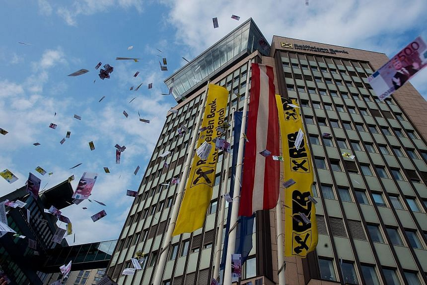 Fake money being tossed in the air during a protest against money laundering in front of the headquarters of Raiffeisen Bank International (RBI) in Vienna, Austria, on Wednesday. Leaked documents published on Sunday suggest that 140 politicians and o