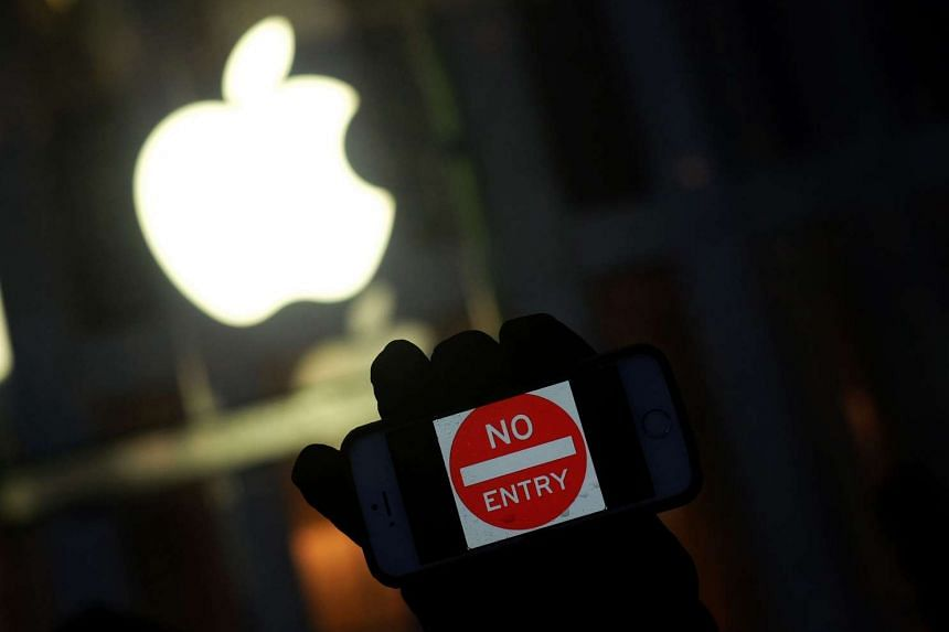 """An anti-government protester holds his iPhone with a """"No Entry"""" sign during a demonstration in February 2016."""