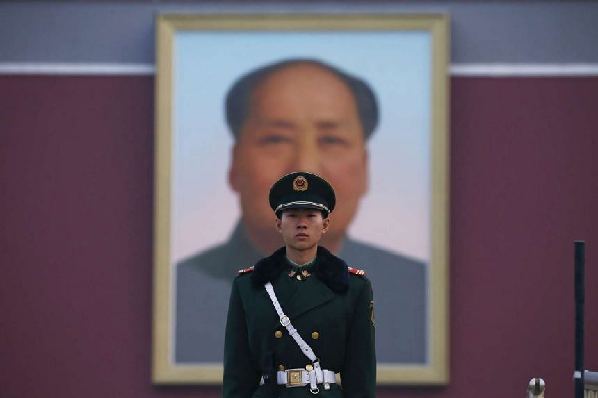 A paramilitary policeman standing guard in front of a portrait of the late Chinese strongman Mao Zedong at the Tiananmen Gate in Beijing on March 3.