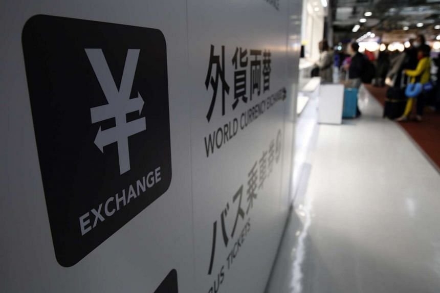 A Japanese Yen currency sign is seen at a currency exchange office as people line up to exchange money at Narita International airport, on March 25, 2016.