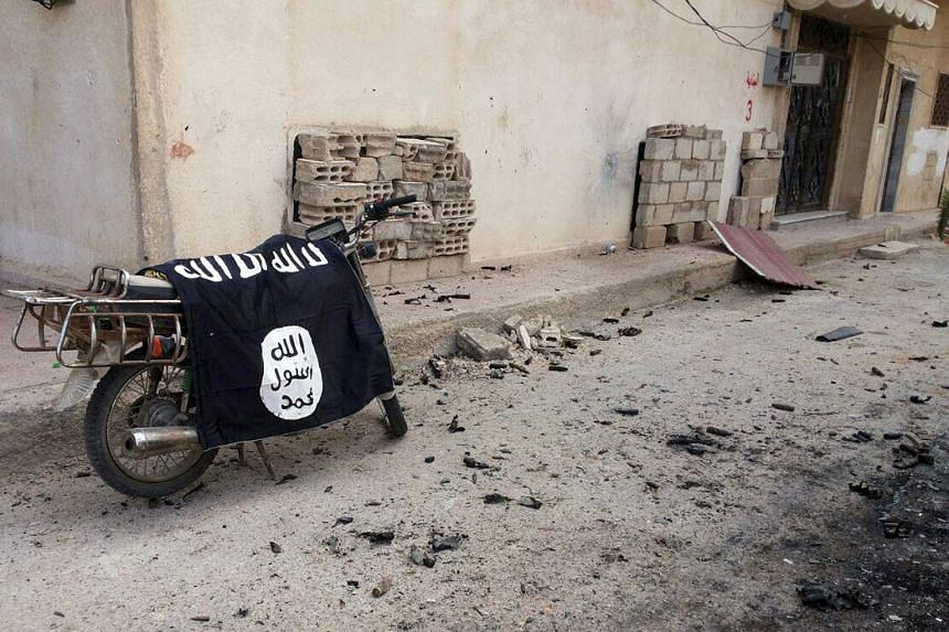 A flag belonging to ISIS fighters is seen on a motorbike after forces loyal to Syria's President Bashar al-Assad recaptured Palmyra, in this handout picture provided by SANA on March 27, 2016.