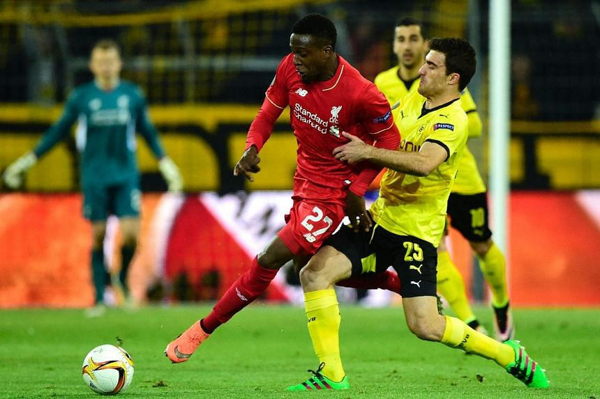 Liverpool's Belgian striker Divock Origi (left) and Dortmund's Greek defender Sokratis vie for the ball.