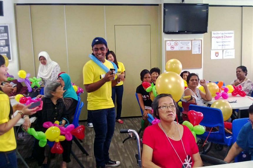 A student from Ngee Ann Polytechnic's School of Humanities and Social Sciences having fun with the elderly at the Lions Befrienders Ghim Moh Senior Activity Centre.