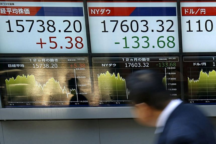 A man walking past electronic boards showing the Japan's Nikkei average (left) and the exchange rate between Japanese yen against the US dollar (right) outside a brokerage in Tokyo, Japan, on April 6, 2016.