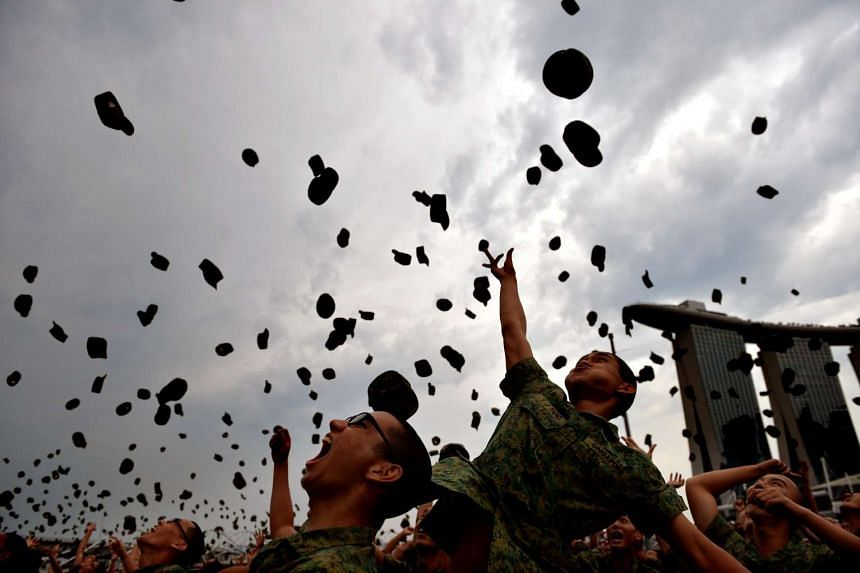 Soldiers throwing their jockey caps in the air to celebrate the end of their basic military training, at the Marina Bay Floating Platform, on April 12, 2014.