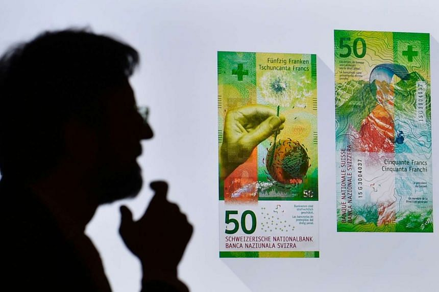 A man silhouettes against an image of the new fifty Swiss franc banknote on April 6, 2016 in Bern.