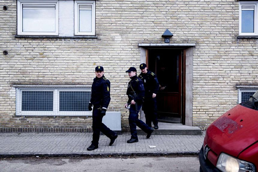Policemen walk out from an apartment block during a search for suspects believed to have travelled to Syria to join the Islamic State, in Tingbjerg, Copenhagen, on April 7, 2016.