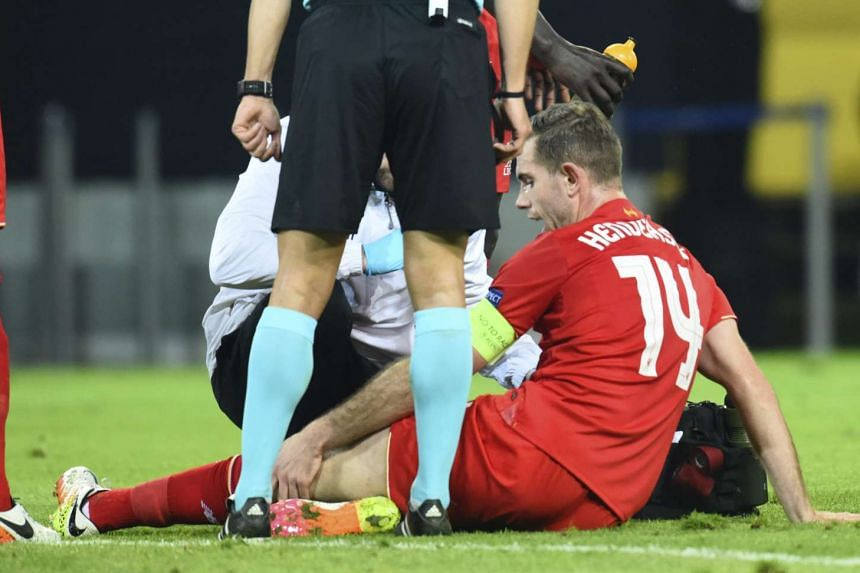 Liverpool's Jordan Henderson (right) sits injured on the field as he is assisted by head coach Juergen Klopp (centre, in white, obscured) on April 7, 2016.