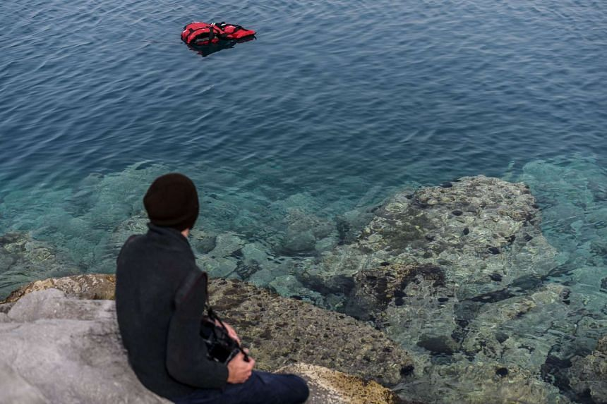 A man looks at a life jacket floating on the sea near the port of Dikili district, where a Turkish ferry carrying second group of deported migrants should arrive.