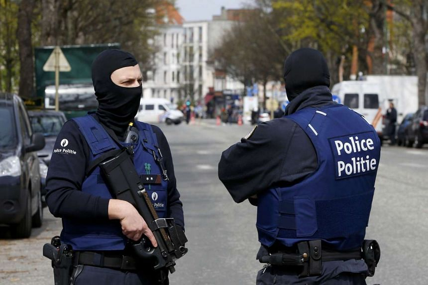 Belgium police officers secure the access during a police operation in Etterbeeck, near Brussels, Belgium on April 9, 2016.