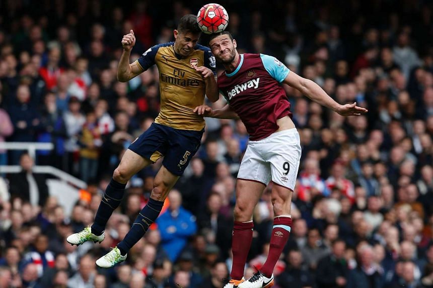 Arsenal's defender Gabriel (left) vies in the air with West Ham United's striker Andy Carroll in the English Premier League football match on April 9, 2016.