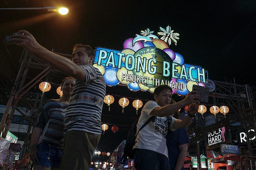 Tourists on a street near Patong beach in Phuket on March 29. Police chief Chakthip Chaijinda said yesterday the warning was real, but called for calm as Thailand gears up for its crowd-pulling Songkran festival next week.