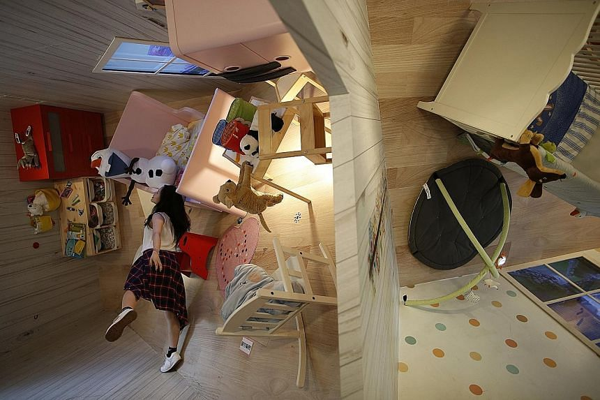 A visitor posing in a three-storey upside-down family-sized house at Huashan Creative Park in Taipei, on Thursday. Featuring over 300 sq m of floor space - filled with home furnishings - it was created by a group of Taiwanese architects at a total co