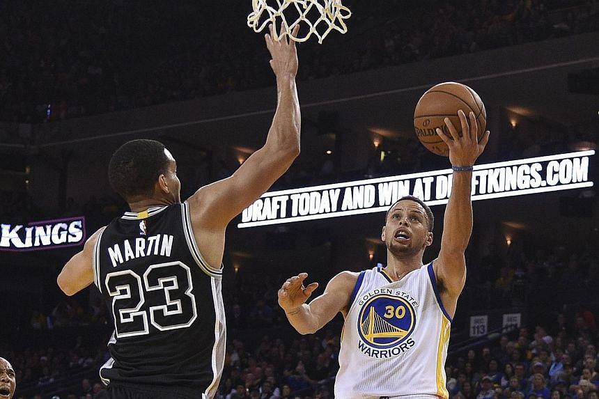 Golden State's Stephen Curry driving to the basket against San Antonio's Kevin Martin during the third quarter at the Oracle Arena. The Warriors defeated the Spurs 112-101 and became just the second team in NBA history after the Chicago Bulls to win