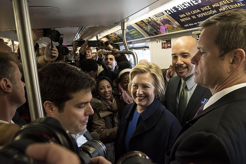 Mrs Clinton riding the No. 4 train with Bronx president Ruben Diaz Jr (behind her) during campaigning on Thursday in the borough of New York City. The latest salvos between Mrs Clinton and Mr Sanders foreshadow a more negative phase heading into the