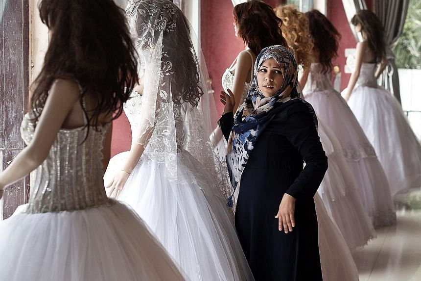 A Palestinian woman shopping for a wedding dress, a requirement for a lavish wedding on which young couples are expected to spend up to $27,000. It can take newlyweds several years to pay off the debt.