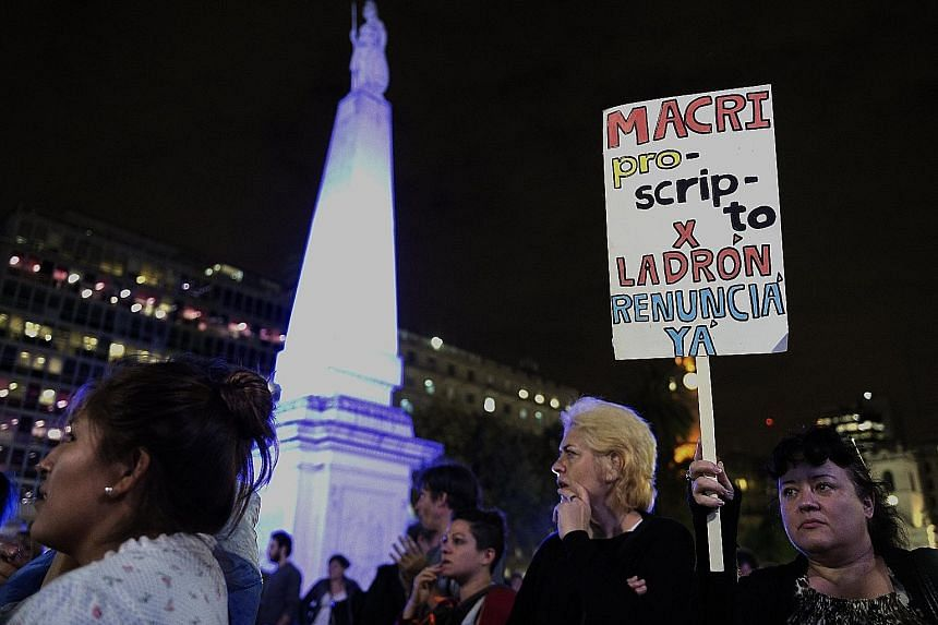 """A protester with a sign reading """"Macri outlaw for thief. Resign now"""" during a demonstration in Buenos Aires against President Mauricio Macri over his offshore financial dealings leaked in the Panama Papers."""