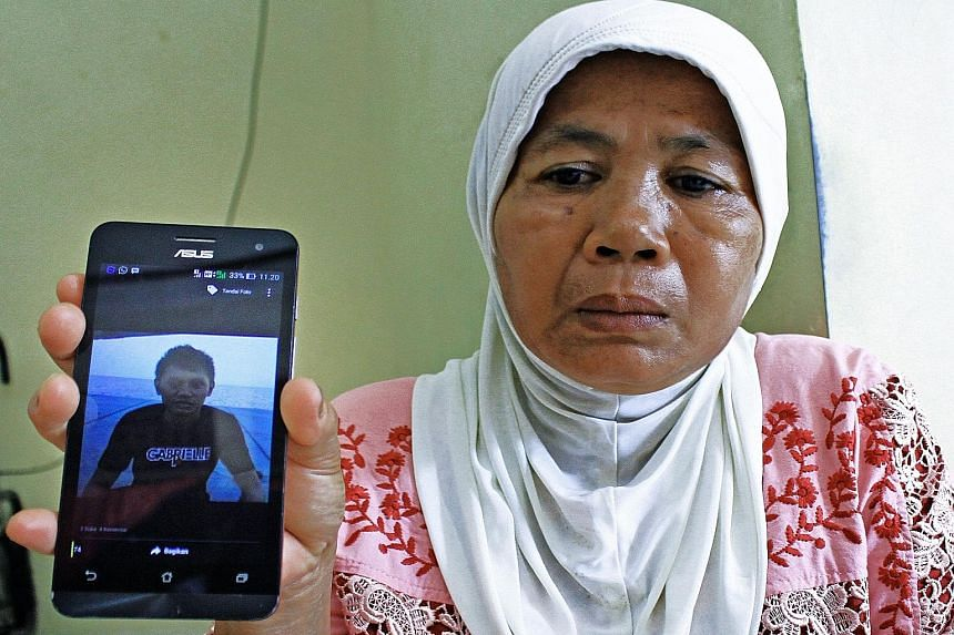 Ms Asmizar holding up a mobile phone on March 31 in Padang, West Sumatra province in Indonesia, showing a photograph of her son Wendy Rahadian - one of 10 members of a tugboat crew kidnapped by Islamic militants in the Philippines. The Indonesian sai