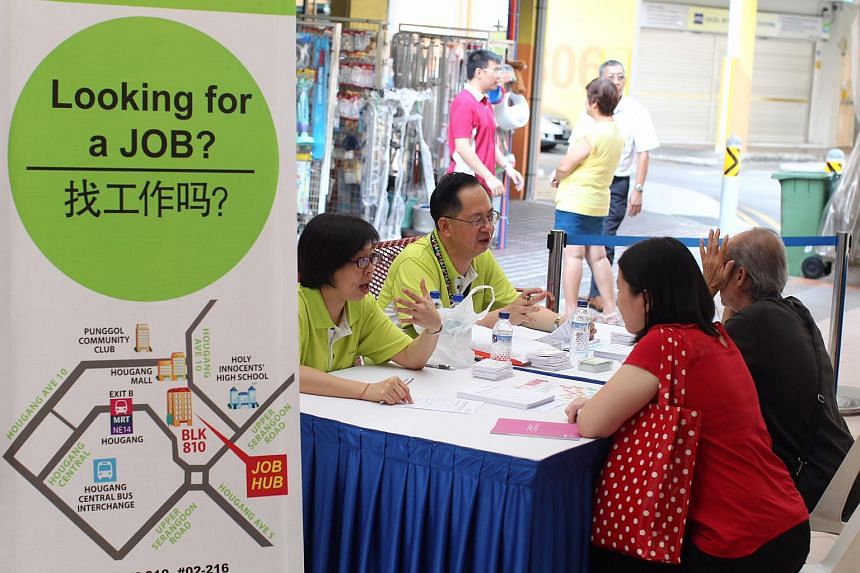 Two women talking to recruiters at the job fair organised by the North East Community Development Council at Hougang Central Court on April 16, 2014.
