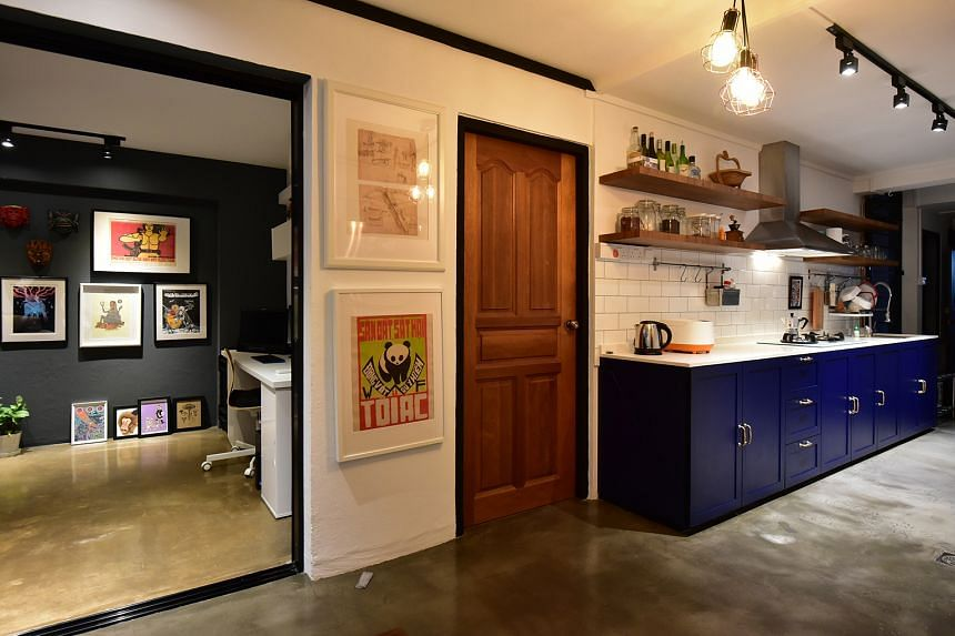 Blue cabinets flank a wall in the kitchen (above) of the three-room flat.