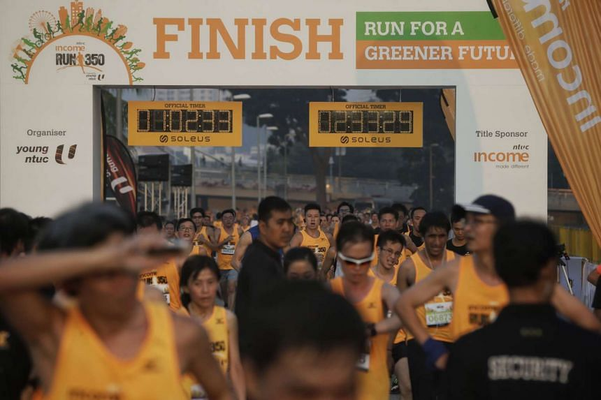 Participants of the NTUC Income RUN 350, organised by Young NTUC, crossing the finish line at F1 Pit Building on April 10, 2016.