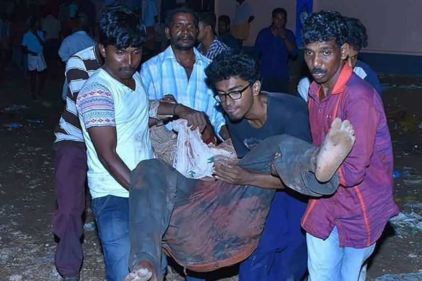 Indian bystanders carrying an injured man after an explosion and fire at the Puttingal Devi Temple in Paravur on April 10, 2016.