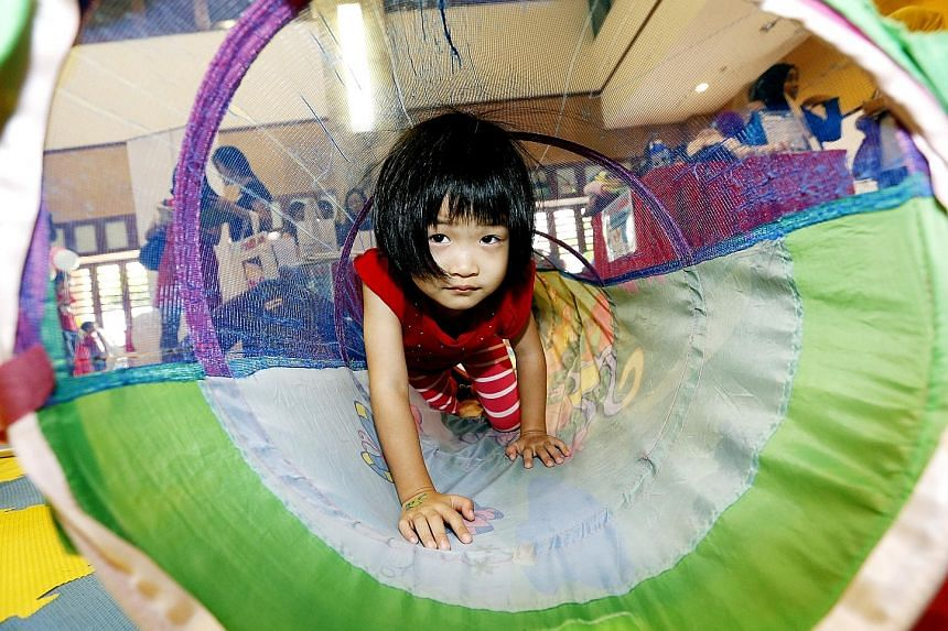 Four-year-old Lim Zi Wei crawling through a play tunnel at the annual Baby Singapore fair at the Fuchun Community Club yesterday. She was among 55 other toddlers and babies there with their parents. The little children, who are between six months and