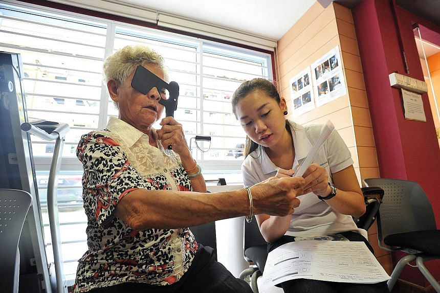 Madam Toh Sim Thiang, 73, getting her eyes checked by nurse Yolane Chew, 24, in the mobile clinic yesterday. Of the 1,800 seniors screened under the project, 1,000 need follow-up treatment. They have been given referrals to seek treatment at hospital