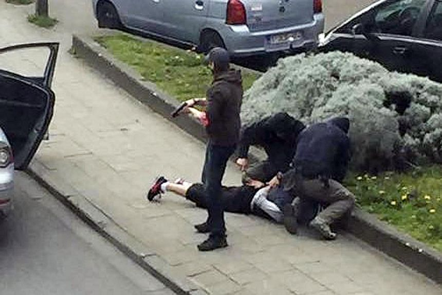(Above) Police officers are seen detaining a suspect during a raid in Anderlecht, near Brussels, last Friday in this still image taken from video footage.
