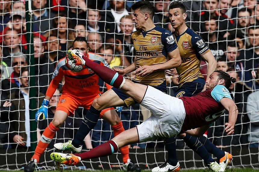 Andy Carroll acrobatically volleying into the corner for West ham's second goal. The English striker scored an eight-minute hat-trick as West Ham's last London derby at Upton Park ended in a frenetic 3-3 draw with Arsenal.