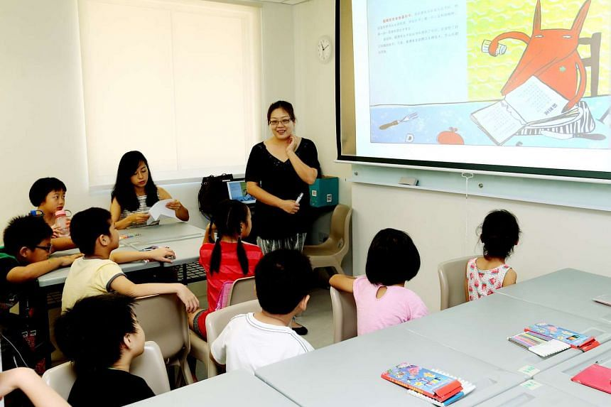 Ms Xu Yang (sitting) and Ms Dong Li, both volunteer Chinese teachers, teaching a class at the official opening of the relocated Chinese Development Assistance Council at Woodlands.