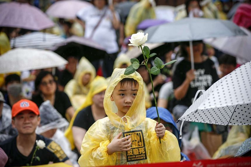 """A Taiwanese boy holds up a white flower and a sticker reading """"Death penalty is necessary"""" during a protest in Taipei on April 10, 2016."""