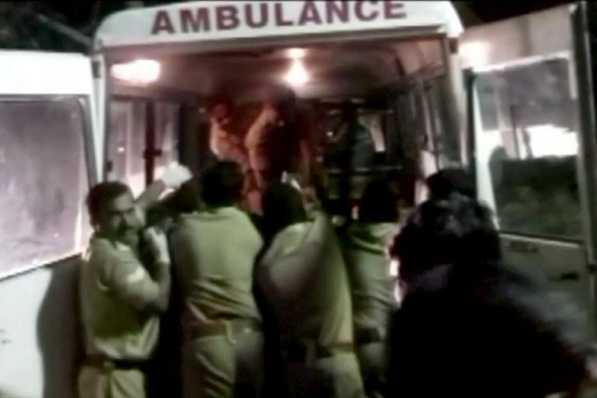 Police rush injured into an ambulance after a fire broke out as people gathered for a fireworks display at a temple in Kollam, southern India, on April 10, 2016.