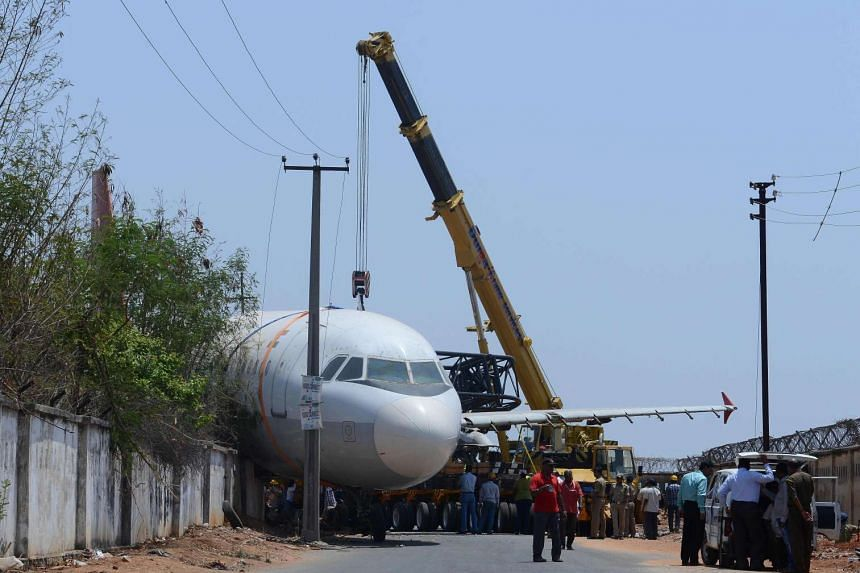 Indian police and rescue officials gather in front of a disused Air India passenger plane which fell from a ground transporter while being moved near Begumpet Airport in Hyderabad on April 10, 2016.