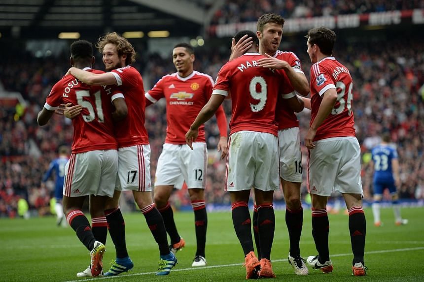 Manchester United players celebrate scoring the opening goal during the English Premier League football match between Manchester United and Everton.