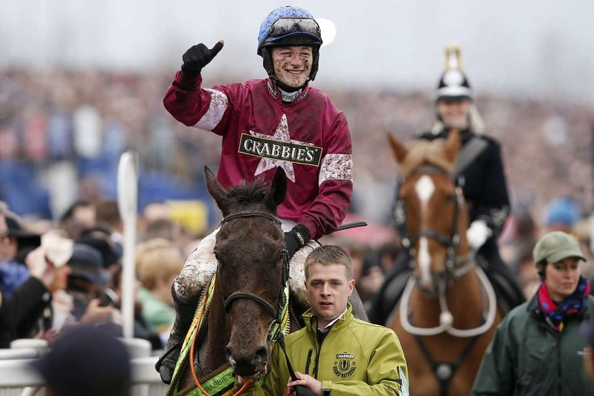 Jockey David Mullins celebrates winning the Grand National on Rule The World.