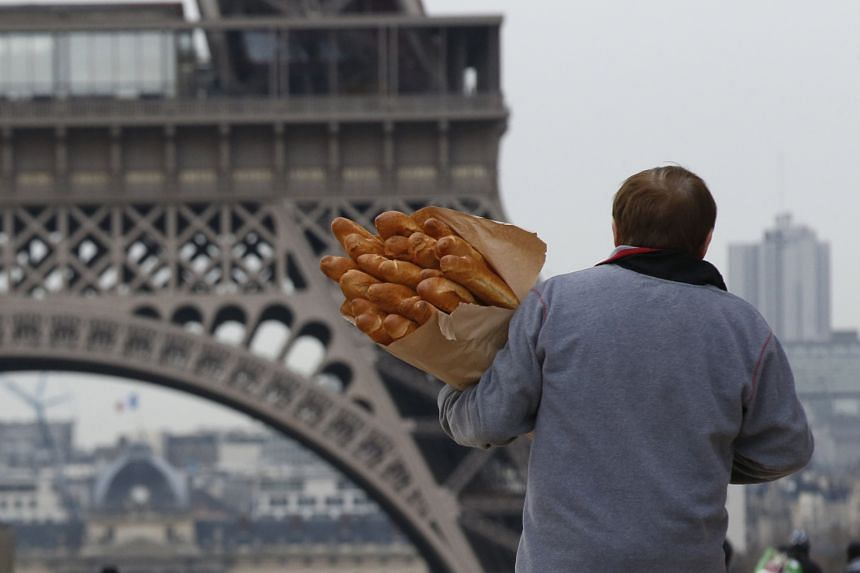 A man with loaves of baguette near the Eiffel Tower in Paris, France.