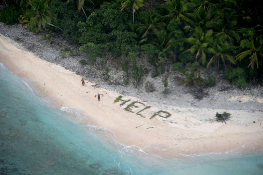 """Two of three men stranded on an island in Micronesia waving life jackets, with palm fronds on the sand spelling the word """"HELP"""", on April 7, 2016."""