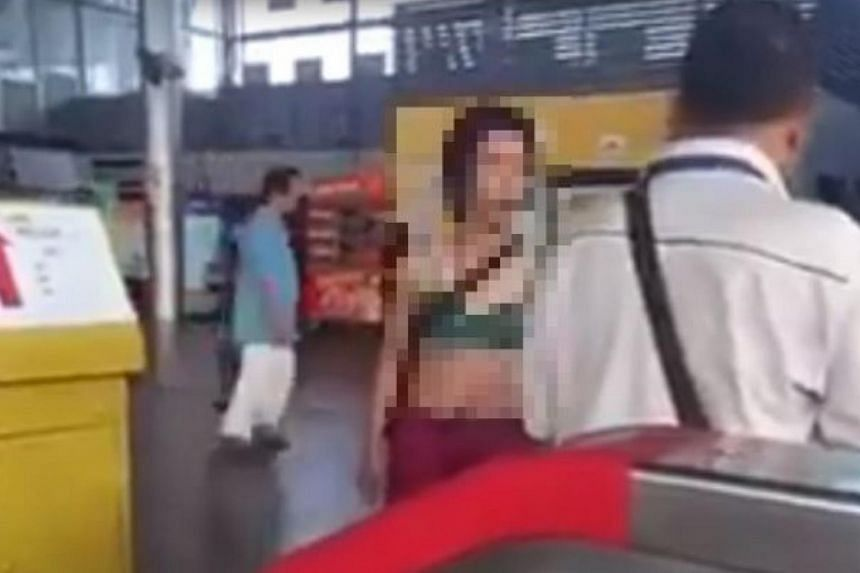 A video of a woman wearing a green bra and pink hot pants arguing with a man at a Malaysia train station has gone viral.