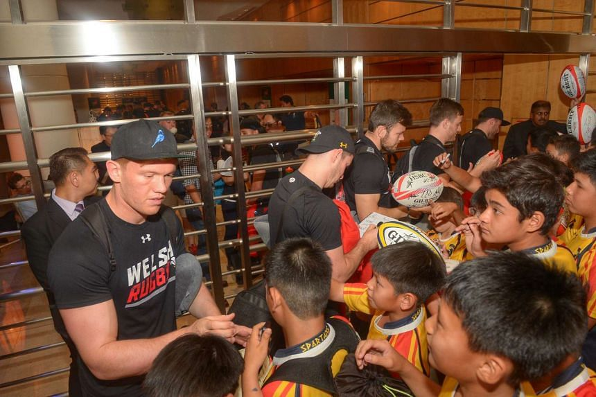 Welsh rugby player, Sam Cross, signing autographs with boys from the Spartans Rugby Club, after arriving in Pan Pacific hotel.