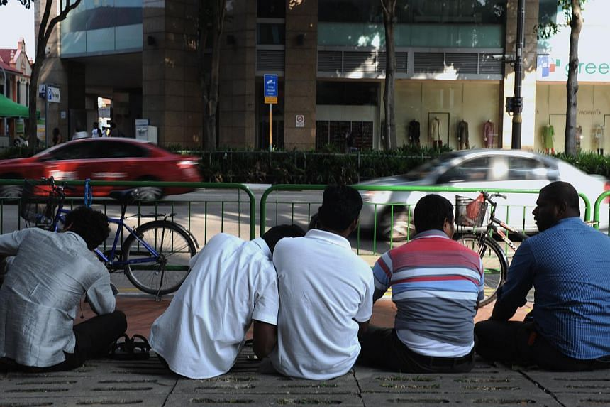 Migrant workers sitting on the ground by the footpath.