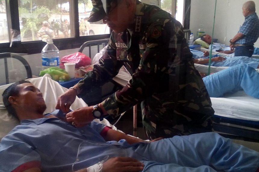 Filipino Armed Forces Chief of Staff General Hernando Iriberri visits an injured soldier in a military hospital in Zamboanga City.
