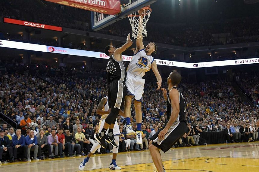 Klay Thompson (in white) of the Golden State Warriors attempts a slam dunk over Danny Green of the San Antonio Spurs in the first quarter of their match on April 10.